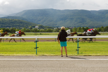 Horse racing. The woman at the racetrack looks at the galloping horses.