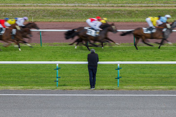 Horse racing. The man at the racetrack looks at the galloping horses. Shot of a man without a face standing with his back