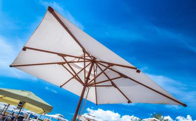 Sun umbrella in white against a blue sky