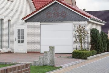 Weiß gemauerte Garage mit Tor