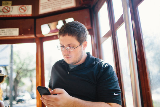 Young man looks at his phone while riding streetcar