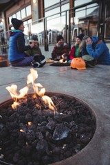 Group of skiers sitting at fire place