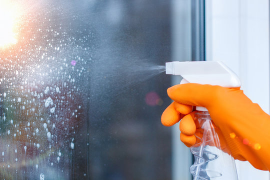 Worker cleans the Windows with spray .