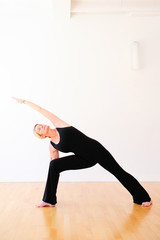 Woman in yoga posture in black dress