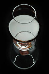 A glass of cognac on a black background with reflection, top view