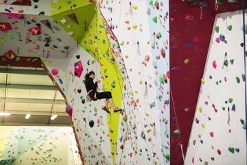 Woman practicing rock climbing on artificial climbing wall
