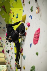 Man practicing rock climbing on artificial climbing wall