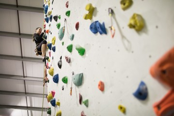Woman practicing rock climbing on artificial climbing wall