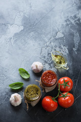 Two types of pesto sauces. High angle view on a grey stone background with copyspace, vertical shot