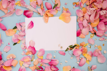 Valentines day or wedding mock up scene with blank card. Floral border of fresh flower petals