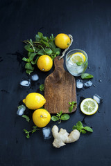 Wooden board with lemons, mint leaves, ginger, ice cubes and mineral water.Lemonade or mojito ingredients