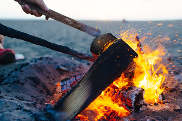 Close-up of woman's hand burning campfire at beach
