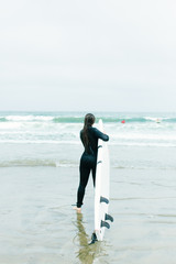 20-something female walks into ocean to surf in San Francisco, California