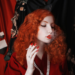 A woman with red hair in a red fitting dress with a cigarette in her mouth. Red-haired girl with pale skin and blue eyes with a bright unusual appearance with beads around her neck. Noir image