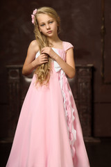 Beautiful young blonde girl with long hair in a pink