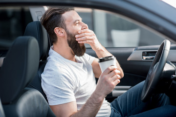 Tired man yawning on the front seat of the car holding coffee to go Wall mural