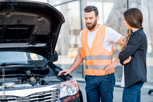 Handsome service worker consulting or providing technical assistance of the broken car to the businesswoman standing near the service center building
