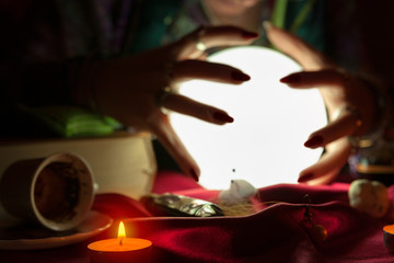 Hands of fortune teller woman around crystal ball