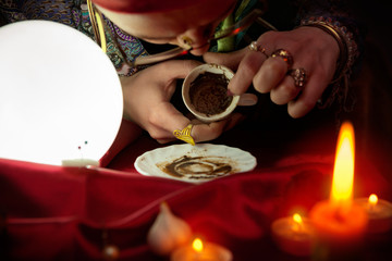 Woman fortune teller looking in empty coffee cup