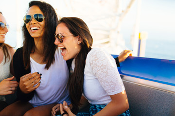 20-something females laugh together on ferris wheel in Pacific Park in Santa Monica Pier, Santa Monica, California