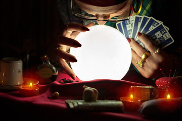 Old woman staring at crystal ball and holding a tarot cards