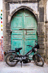 moroccan old door with a bike in the front