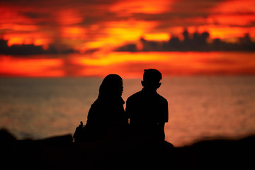 Silhouettes of a young man and a girl sitting on the beach at sunset time