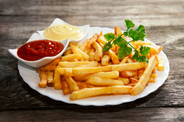 French fries with tomato sauce, mayonnaise and parsley