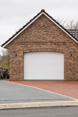Gemauerte Garage mit weißem Tor
