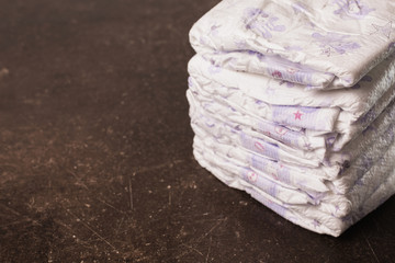 Baby diapers on a dark marble background. Hygiene. Caring for children