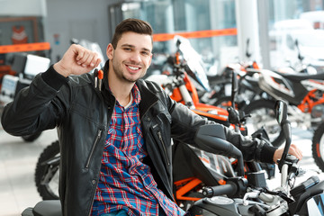 Cheerful owner. Shot of a stunning handsome young man sitting on his new motorbike holding keys smiling to the camera cheerfully at the motorcycle salon