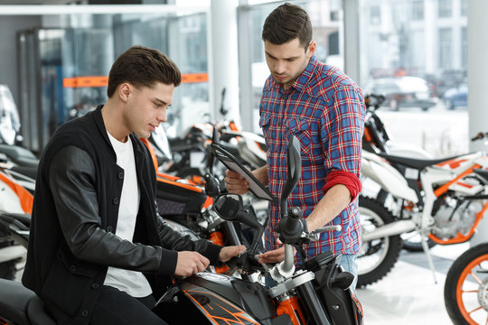 Quality guaranteed. Young male motorcycle salon manager showing his cheerful customer a new motorbike for sale