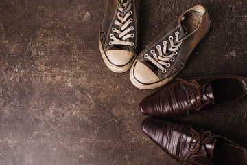 Old black sneakers and brown classic shoes on a dark marble background. Footwear for outdoor activities