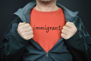 a man showing his t-shirt with the word immigrant on it