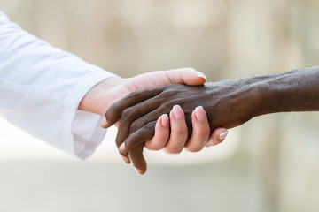 Helping hands.Caucasian doctor woman's hand holding black African man's hand.Unrecognizable people