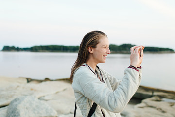 Young woman taking pictures in harbor, Rockland Maine