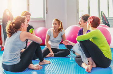 Group of women hanging out after pilates exercise.