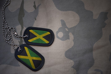 army blank, dog tag with flag of jamaica on the khaki texture background. military concept