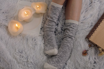 Cozy winter evening , warm woolen socks, soft blanket, candles. Woman relaxing at home, reading a book. Comfy lifestyle.