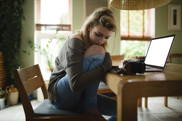 Thoughtful woman sitting with laptop
