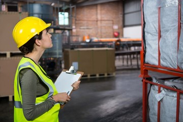 Confident female worker examining products in warehouse