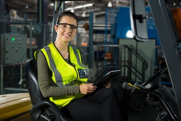 Beautiful female worker with digital tablet in forklift