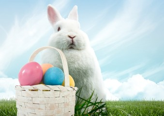Easter rabbit with basket of eggs in front of blue sky