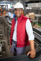 Happy male employee standing by conveyor in factory