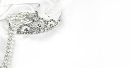Bridal wedding decorations soft white bride background, silver crown and pearls on satin with space for text