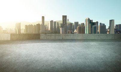 Empty asphalt carpark with modern city skyline , morning sunrise scene .
