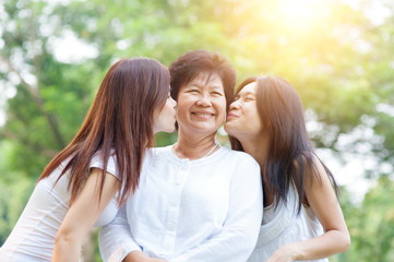 Daughters kissing elderly mother