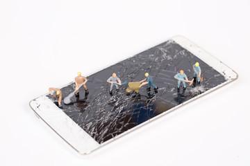 miniature people repair smartphone crack