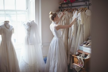 Young bride selecting wedding dress from clothes hanger