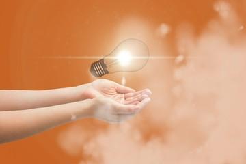 Digital composite image of light bulb over hands